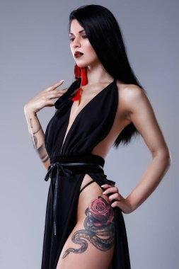 Portrait of woman with tattoos wearing black dress