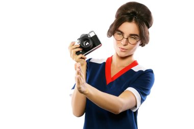 Young woman in vintage style holding retro camera in hands isolated on white background
