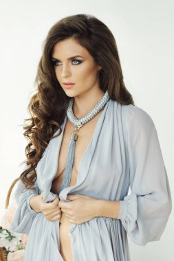 Portrait of young woman wearing stylish necklace and beautiful dress