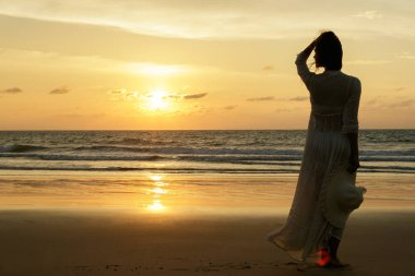 Woman wearing beautiful dress and hat on beach during sunset time