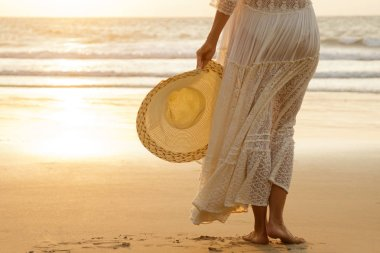 Woman wearing beautiful white dress and hat on the beach during sunset time