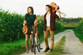 Fotografie Young couple walking on country road. Girl riding bicycle and guy is holding guitar.