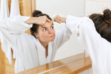 Woman squeeze pimples in the bathroom