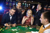 Happy rich people celebrating successful poker game in the casino