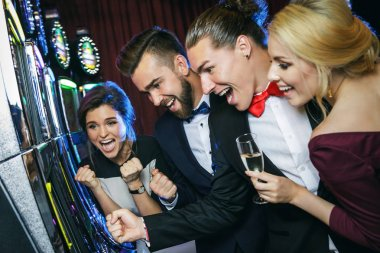 Group of friends playing slot machines in casino