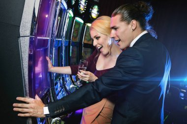 Young and positive couple playing slot machines in the casino
