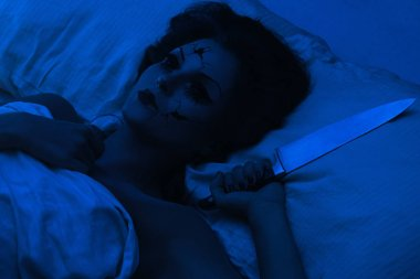 Creative image for Halloween. Spooky porcelain speaking doll holding knife and lying in the bed.