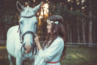 Young woman in beautiful white dress with beautiful horse