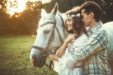 Young couple taking care about  beautiful horse