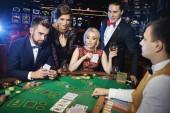 Skupina mladých bohatých lidí hraje poker v kasinu