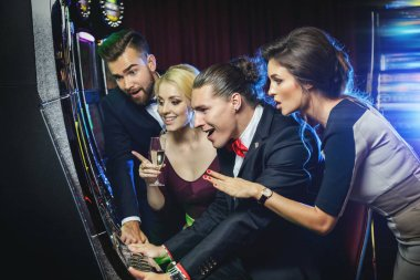 Group of friends playing slot machines in the casino