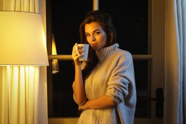 Beautiful woman wearing warm sweater with a cup of hot drink
