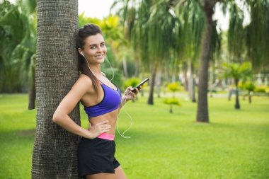 Woman in earphones listening music during her workout
