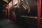 Dva silní muži cviči na barech v tělocvičně