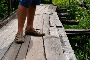 Wooden rural bridge over a river in green woods for tourists to walk along. Wood pathways. Tourist walk.