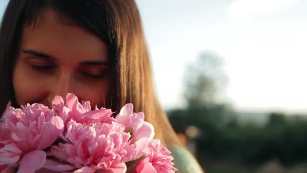 Slow motion of portrait of a young beautiful woman with a bouquet of peonies.