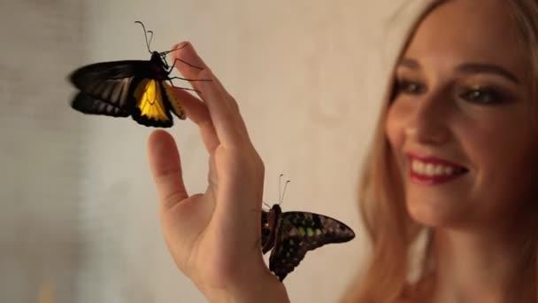 junge charmante Frau lächelt und betrachtet lebende Schmetterlinge auf ihrer Hand.