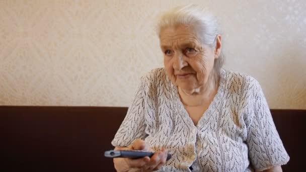 Az öregasszony átvált a Tv csatornát a távoli, és mosolyog. Grandmas Tv-nézés.