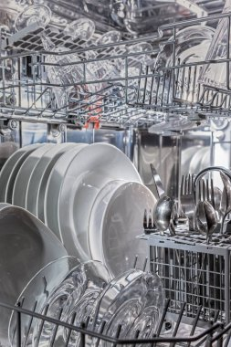 Open dishwasher with clean dishes, close up, cold light