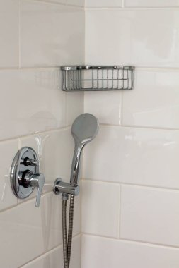 Silver metal shiny faucet  shower watering can water switch in the shower cubicle hotel home bathroom with white tiles and with a metal shelf on the wall. Bathroom luxury interior