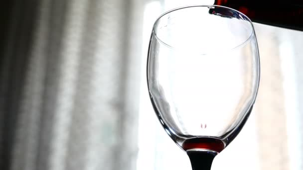 red wine pouring into a glass on light background