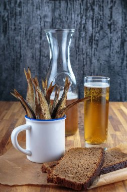 close-up shot of light beer and dried fish on wooden tabletop