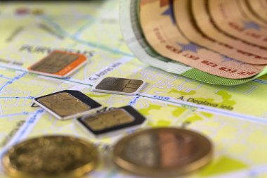 Close-up gsm cards of different sizes lie on the city map surrounded by coins and Euro banknotes. Selective focus.