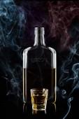 Üveg Mescal és egy pohár Mescal, izolált fekete háttér füst és reflexiók. 100 élesség.