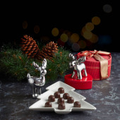 Photo Plate in the form of a Christmas tree with chocolates on the background of figures of Christmas reindeer, gifts and a wreath with cones. space for your text.