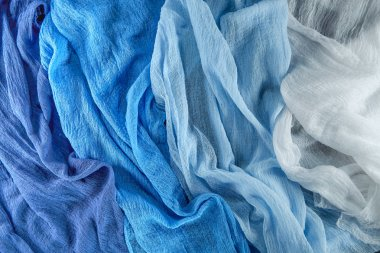 Beautiful fabric for decoration and sewing different shades of the same color scheme. Texture of the gauze of blue shades.