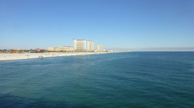 rippled sea surface with dustant buildings under blue sky