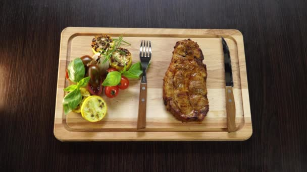 Grilled pork steak with vegetables on a wooden board with kitchen appliances 4k video