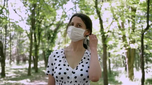 Young woman in summer Park enjoying fresh air removing protective medical mask with face from allergies or virus