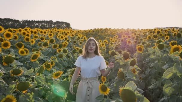 Šťastná mladá žena skočí do pole slunečnic na slunné letní den se směje baví s rukama na čerstvém vzduchu