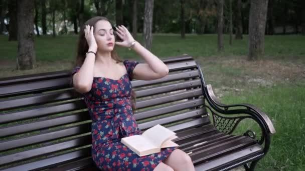 Mladá žena v parku sedí na lavičce s knihou a upravuje si vlasy