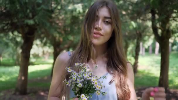 happy smiling young woman walking in park with small bouquet of flowers in hands