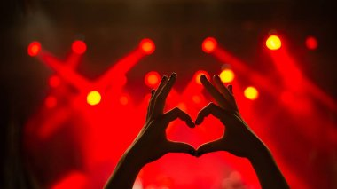 Girl showing heart-shape symbol enjoying her favorite group on the concert