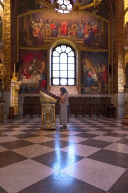 MOLDOVA - Curchi, August 18, 2018: woman in age praying at the icon in the Inside of the Curchi Monastery, Orhei, Moldova, Europe