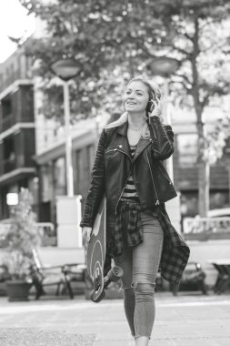 black and white image of beautiful smiling girl in leather jacket and headphones holding skateboard and walking on street