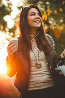 low angle view of happy young woman in earphones holding coffee to go and walking in park
