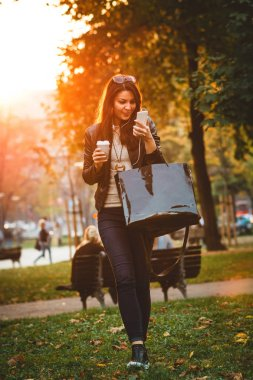 smiling young woman with handbag and coffee to go walking in park and listening music with smartphone at sunset