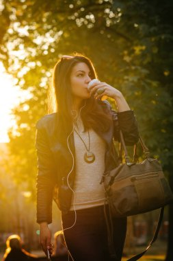 young woman in leather jacket drinking coffee from paper cup and listening music with smartphone while walking in park at sunset
