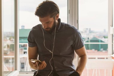 handsome bearded man in earphones sitting on windowsill and using smartphone