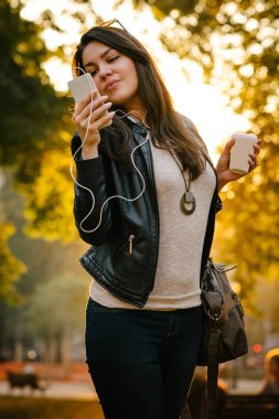 attractive girl in leather jacket holding coffee to go and listening music with smartphone in park at sunset