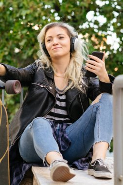 low angle view of smiling blonde girl in headphones sitting with skateboard and using smartphone
