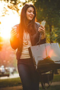 beautiful smiling girl in leather jacket holding coffee to go and listening music with smartphone at sunset