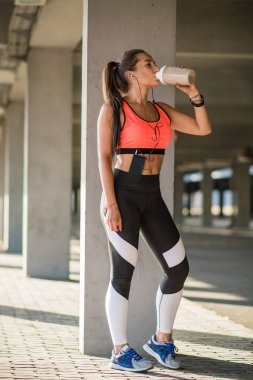 young female athlete drinking protein drink