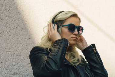 attractive blonde girl in leather jacket and sunglasses standing near white wall and listening music in headphones