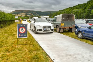 BUILTH WELLS, WALES - JULY 2018: Car driving on metal plates placed on a field being used as a public car park for an agricultural show.