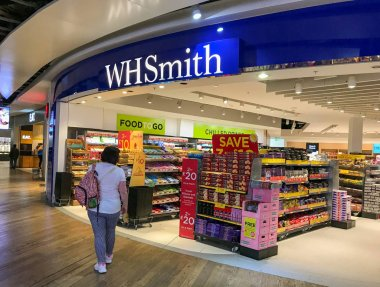 LONDON HEATHROW AIRPORT - JUNE 2018: Person walking past the branch of W.H. Smith newsagents in Terminal 3 at London Heathrow airport.